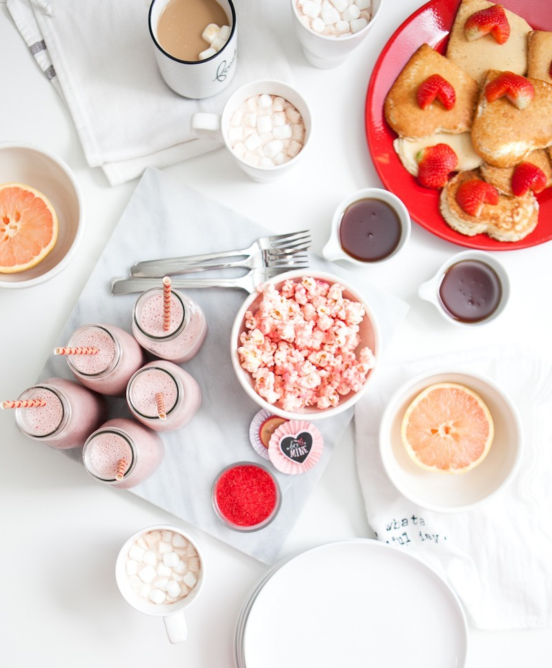 Valentine's Day Brunch that the entire family with love... complete with the cutest EASY heart shaped pancakes and strawberries, pink smoothies and a pink candied popcorn recipe! Host a galentine's brunch or serve your valentines a breakfast they'll remember!