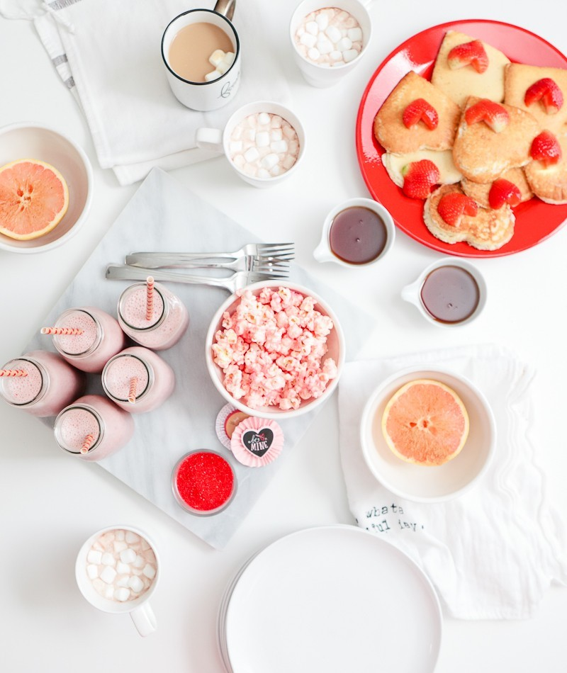 A sweet red and pink Valentine's Day Brunch that the entire family with love... complete with the cutest EASY heart shaped pancakes and strawberries, pink smoothies and a pink candied popcorn recipe! Host a galentine's brunch or serve your valentines a breakfast they'll remember!