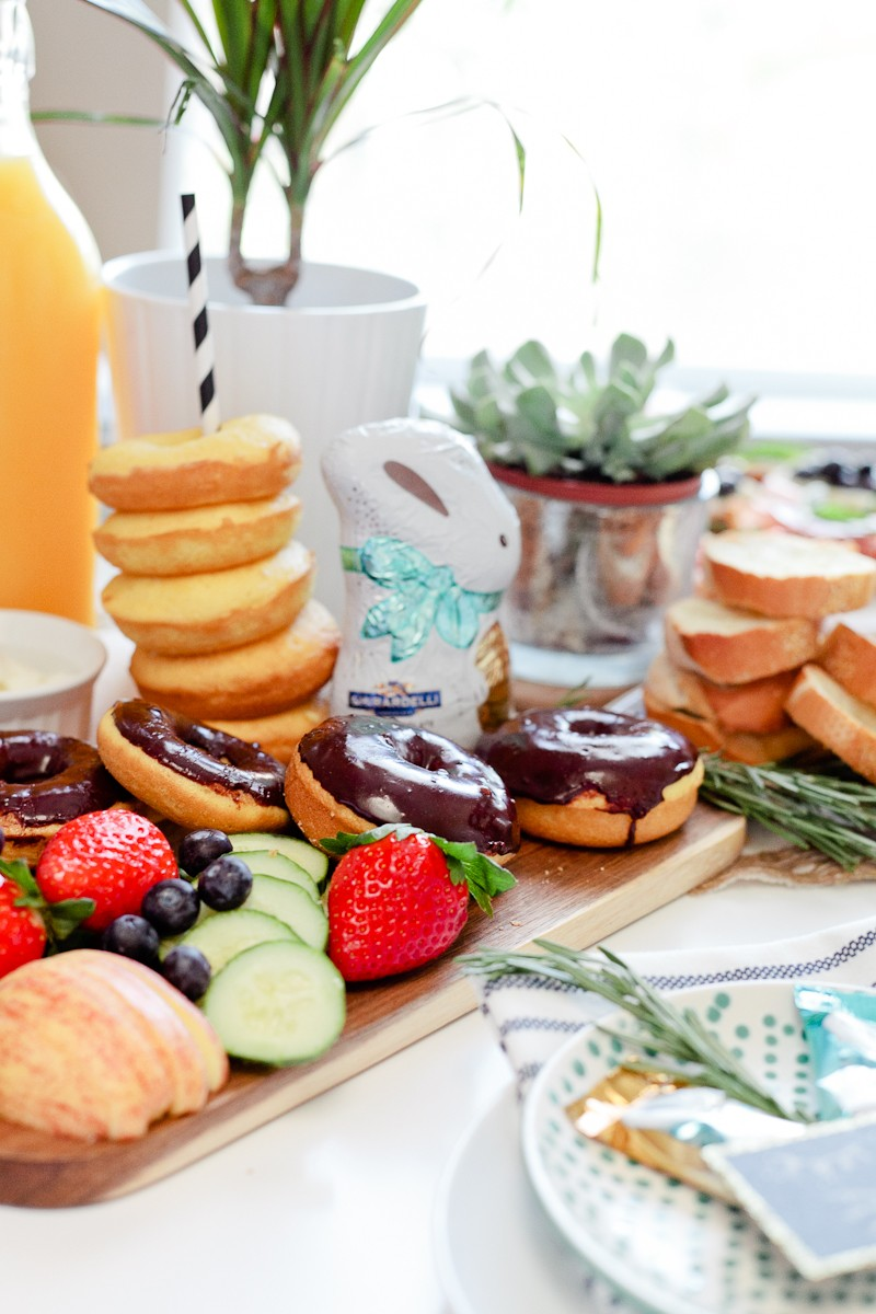 easter brunch ideas   Easter Brunch Ideas by popular Florida lifestyle blog, Fresh Mommy Blog: image of a wooden cutting board filled with cucumber slices, strawberries, blueberries, glazed donuts, chocolate frosted donuts, and a chocolate bunny.