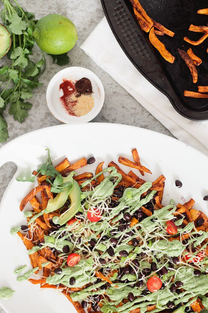 Loaded Sweet Potato Mexican Street Fries with Avocado Lime Dressing! A skinny and delicious twist on a loaded fry platter that won't mess with your waistline or derail your resolutions! Need a dinner to drool over? Try these Loaded Sweet Potato Mexican Street Fries! A skinny and delicious twist on a loaded fry platter that won't mess with your waistline or derail your resolutions! A healthy and hearty recipe from Tabitha Blue of Fresh Mommy Blog with Horizon.