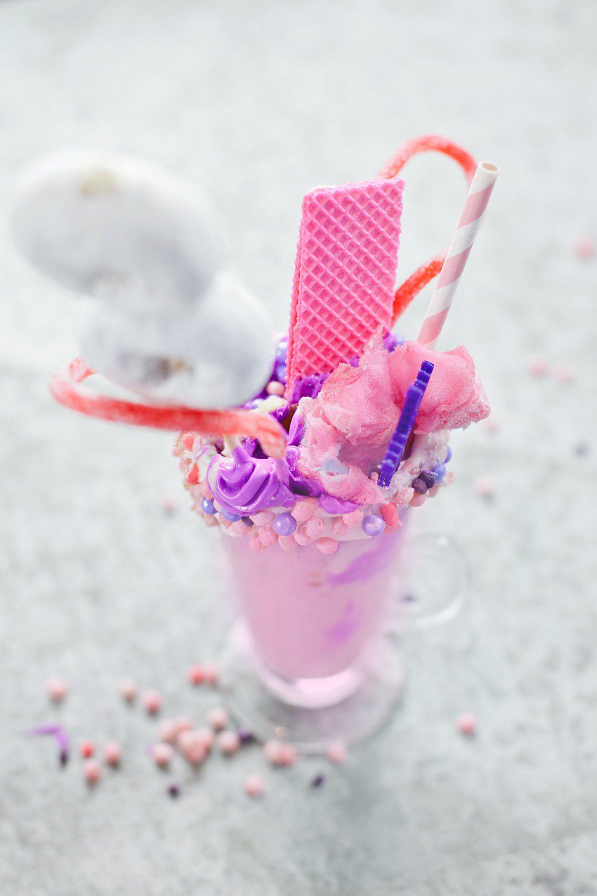 These Epic Royal Crazy shakes are indulgently MAGICAL! A rich, thick strawberry milkshake is topped with a sugaring of sprinkles and candies to make a delicious crazy shake drink fit for a princess... or a prince. A pretty in pink and purple freak shake!