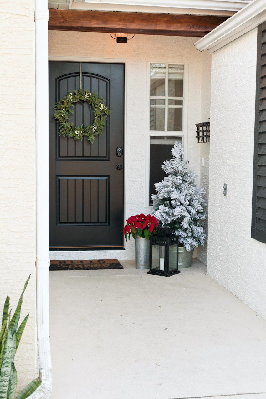 Modern farmhouse front entryway door makeover reveal! Open your front door to guests this Christmas season with an updated front door. Black and white with wood natural elements make a welcoming statement and up the curb appeal.