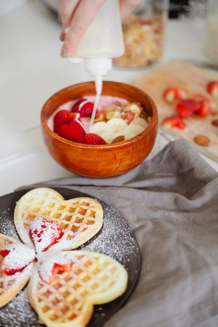 Valentine's Day Breakfast in Bed full of all things sweet, pink and delicious, of course! Heart waffles and strawberries and cream smoothie bowl, that tastes like ice cream, and heart shaped strawberries steal the show in this morning breakfast tray styled for your valentine. - Valentines Day Breakfast in Bed with Strawberry Smoothie Bowl by popular Florida lifestyle blogger Fresh Mommy Blog