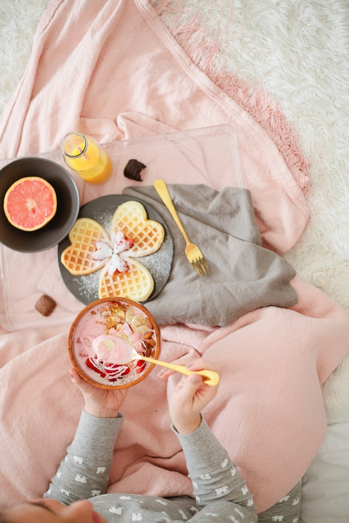 Valentine's Day Breakfast in Bed full of all things sweet, pink and delicious, of course! Heart waffles and strawberries and cream smoothie bowl, that tastes like ice cream, and heart shaped strawberries steal the show in this morning breakfast tray styled for your valentine.
