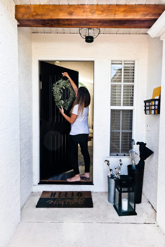 Home Improvement Projects featured by top US home improvement blog Fresh Mommy Blog; Image of a woman hanging a wreath on her front door.