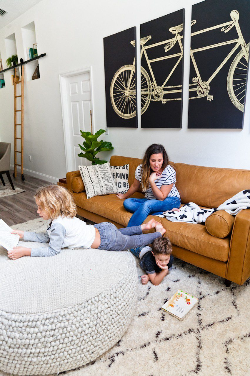 Seeing past dated paint colors, a wall of mirrors, popcorn ceiling and mismatched flooring, this ultimate living room has been completely transformed to a cozy and comfortable open family living space with bold statement pieces like our Article sofa, neutral colors and touches of sleek mid century and Scandinavian inspired design. The ultimate living room makeover before and after for a busy family from popular Florida lifestyle blogger Tabitha Blue of Fresh Mommy Blog.   Article sofa featured in the latest living room makeover by top Florida lifestyle blog, Fresh Mommy Blog