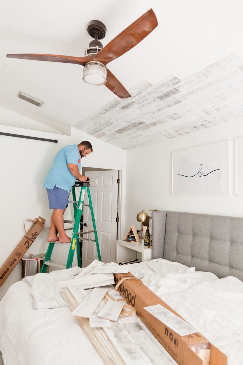 How to Install your Own Reclaimed Wood Ceiling - Master Bedroom Update featured by top Florida lifestyle blog, Fresh Mommy Blog: man installing reclaimed wood ceiling in his master bedroom