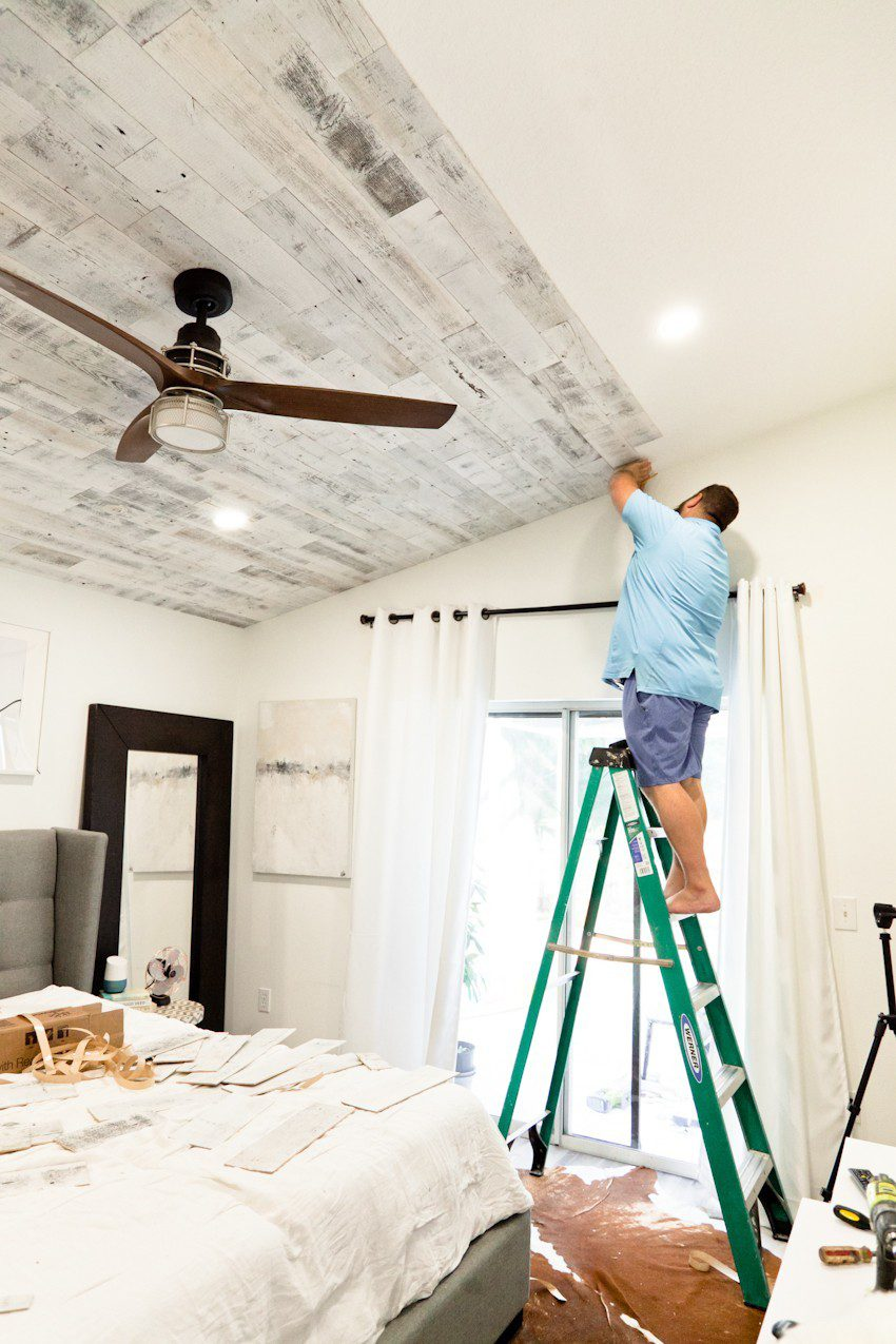 How to Install your Own Reclaimed Wood Ceiling - Master Bedroom Update featured by top Florida lifestyle blog, Fresh Mommy Blog: man installing his reclaimed wood ceiling in his master bedroom