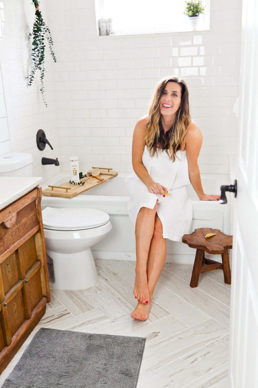 Top Florida life and style blog, Fresh Mommy Blog, features their Winter Hair Care tips: image of a woman in her bathroom holding Pantene Intense Rescue shots