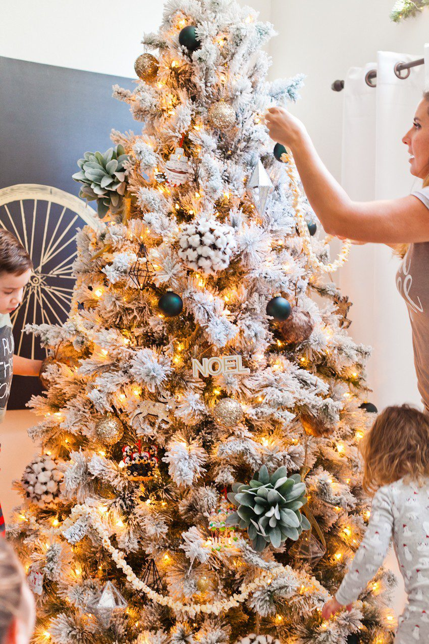 How to Host your Own Festive Tree Trimming Party from top Florida lifestyle blogger Tabitha Blue of Fresh Mommy Blog: image of children putting up their homemade Christmas tree decorations