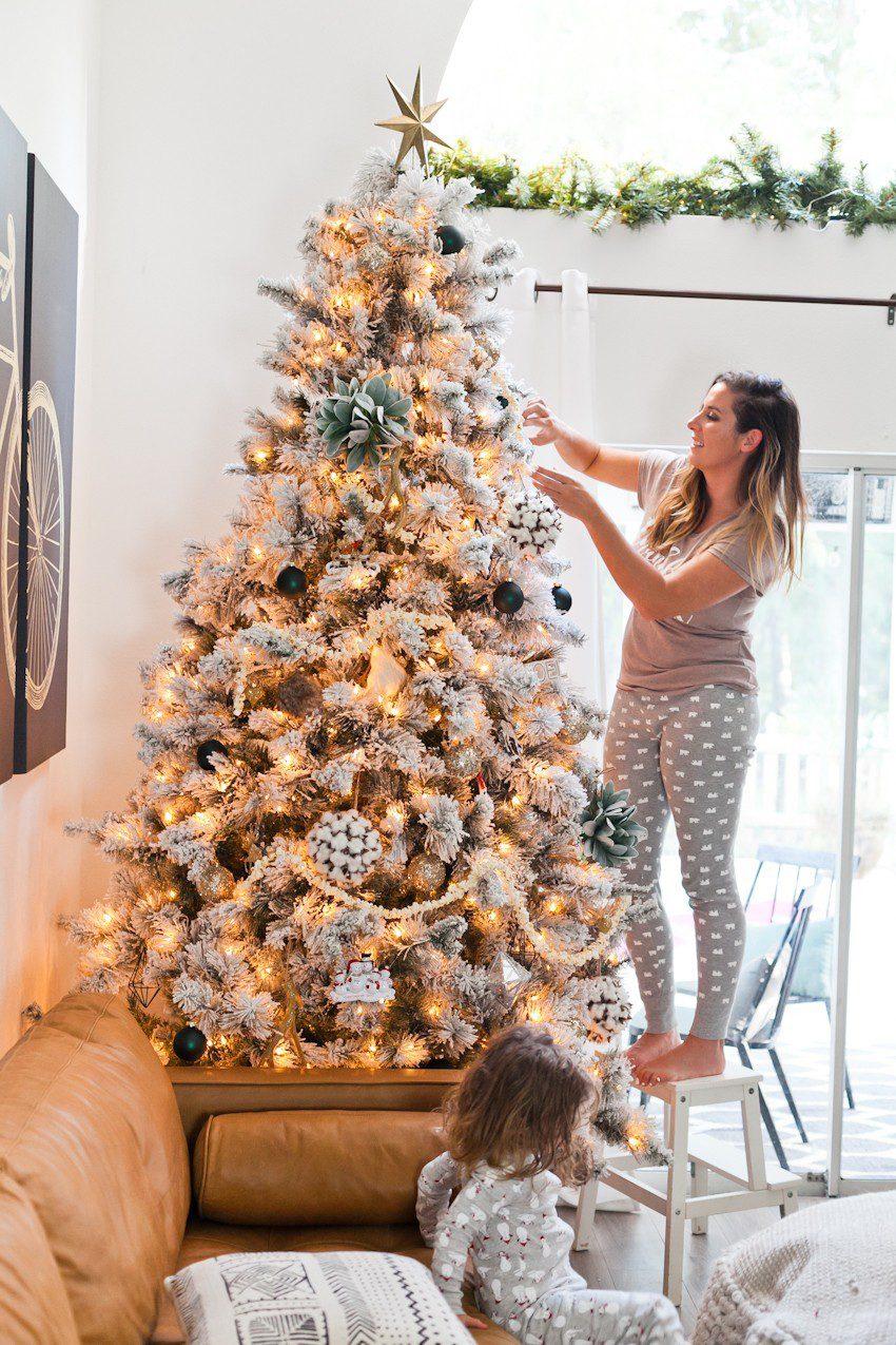 How to Host your Own Festive Tree Trimming Party from top Florida lifestyle blogger Tabitha Blue of Fresh Mommy Blog: image of a woman putting up her homemade Christmas tree decorations