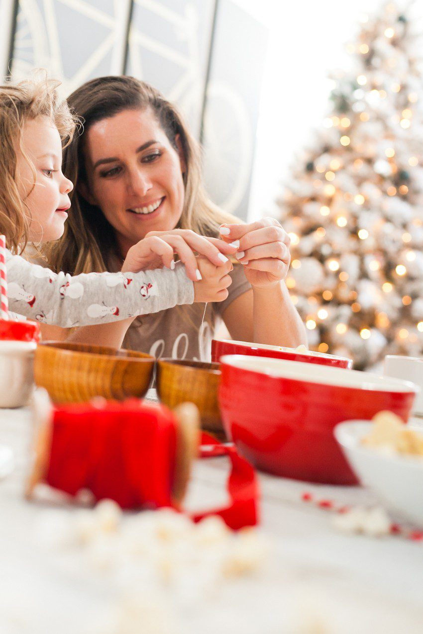 How to Host your Own Festive Tree Trimming Party from top Florida lifestyle blogger Tabitha Blue of Fresh Mommy Blog: image of mom and daughter making Christmas tree decorations with popcorn