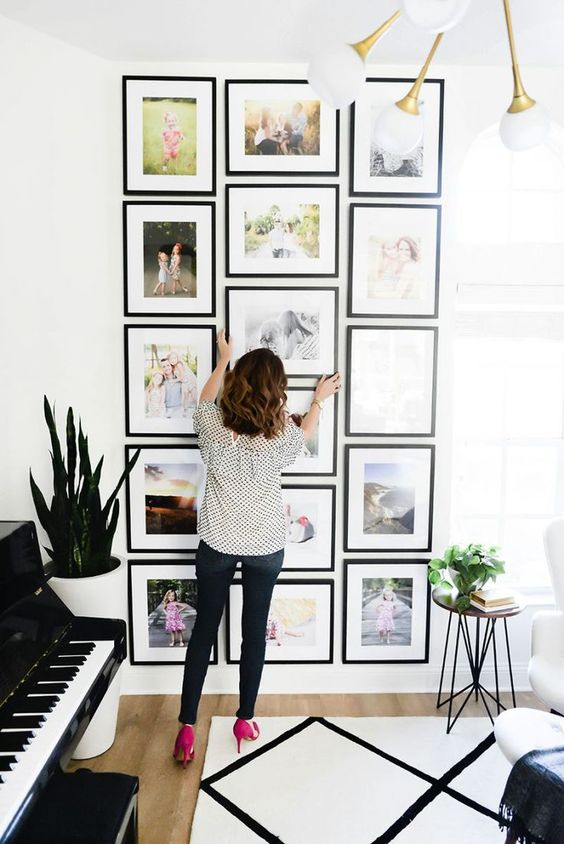 Home Improvement Projects featured by top US home improvement blog Fresh Mommy Blog; Image of a woman hanging photos on the wall.