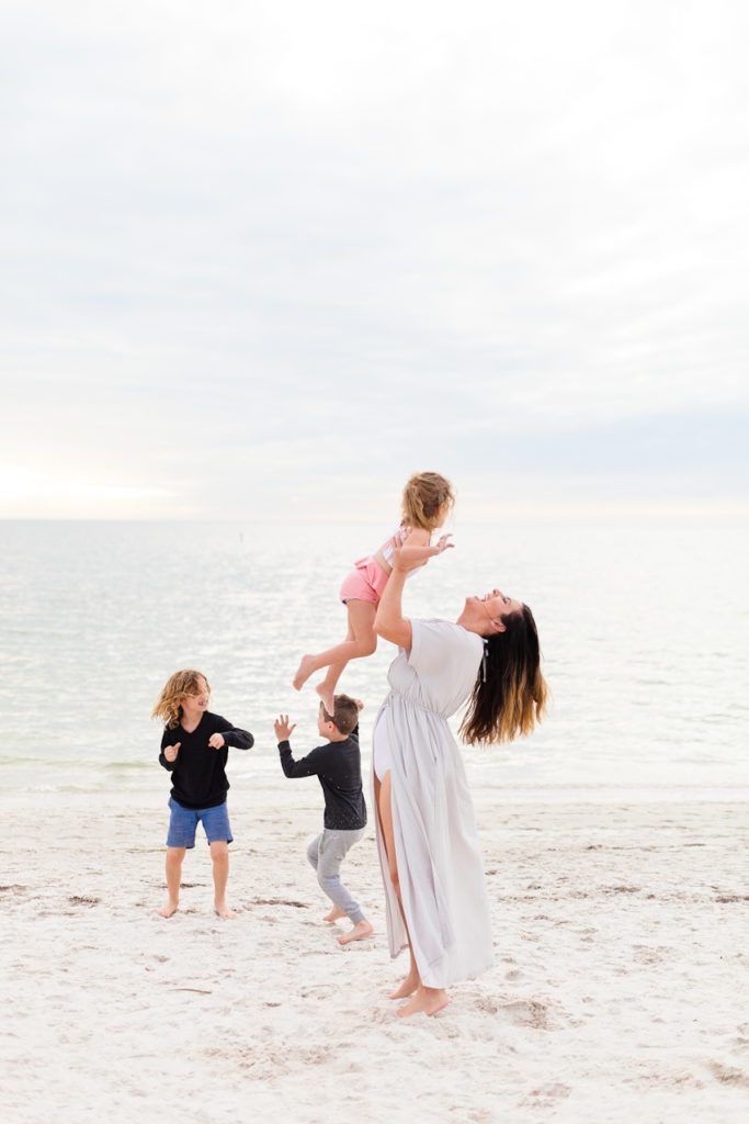 Summer Hair featured by top US life and style blog Fresh Mommy Blog; Image of a woman at the beach with her family.