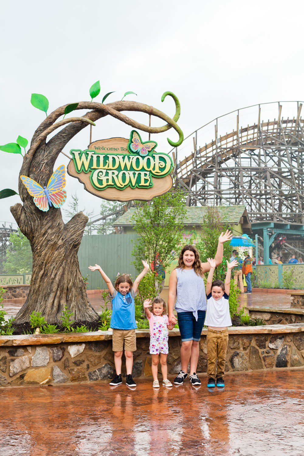 A Day at Dollywood and the new Wildwood Grove | VIDEO with Southern Living and Tabitha Blue of Fresh Mommy Blog | A Day at Dollywood and the new Wildwood Grove | VIDEO with Southern Living by popular Florida travel blog, Fresh Mommy Blog: image of two young girls and two young boys waving and standing under the Wildwood Grove sign at Dollywood park.