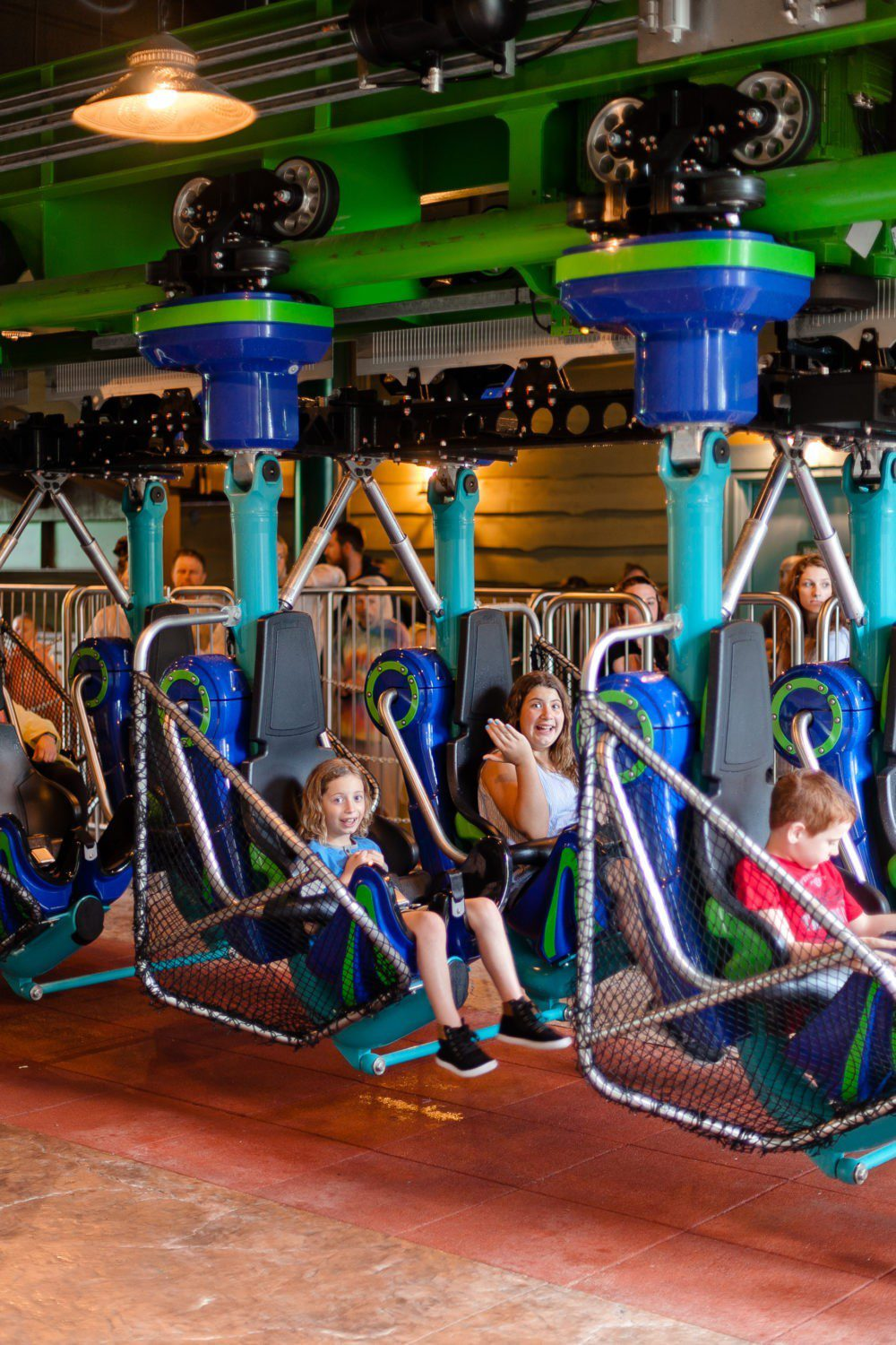A Day at Dollywood and the new Wildwood Grove | VIDEO with Southern Living and Tabitha Blue of Fresh Mommy Blog | A Day at Dollywood and the new Wildwood Grove | VIDEO with Southern Living by popular Florida travel blog, Fresh Mommy Blog: image of 3 young kids sitting on a roller coaster in Dollywood park.