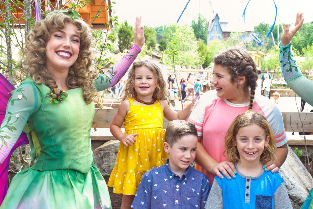 A Day at Dollywood and the new Wildwood Grove | VIDEO with Southern Living and Tabitha Blue of Fresh Mommy Blog | A Day at Dollywood and the new Wildwood Grove | VIDEO with Southern Living by popular Florida travel blog, Fresh Mommy Blog: image of two young girls and two young boys standing next to a fairy at the Wildwood Grove in Dollywood park.