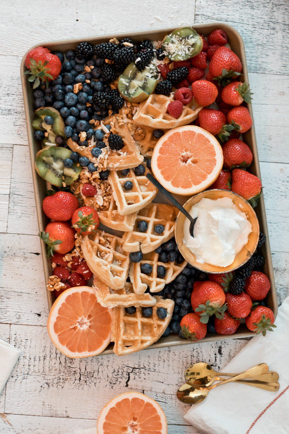 DIY Yogurt Parfait Recipe Ideas with Protein for Kids They'll Love by popular Florida lifestyle blog, Fresh Mommy: image of kiwis, strawberries, blackberries, blueberries, coconut, grapefruits, waffles, and Fage greek yogurt on a tray.