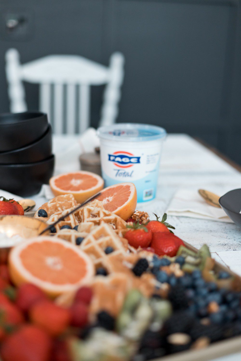 DIY Yogurt Parfait Recipe Ideas with Protein for Kids They'll Love by popular Florida lifestyle blog, Fresh Mommy: image of kiwis, strawberries, blackberries, blueberries, coconut, grapefruits, and waffles on a tray next to a container of Fage greek yogurt.