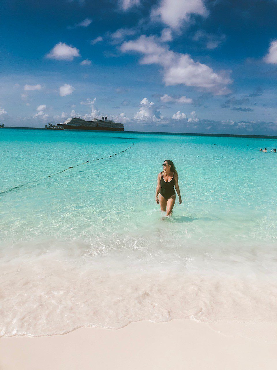 5 Amazing Reason to go on a Holland America cruise with Oprah Magazine by popular US lifestyle blog Fresh Mommy Blog: image of woman wearing a black one piece swimsuit and standing in the Caribbean ocean with a Holland America cruise ship on the horizon.