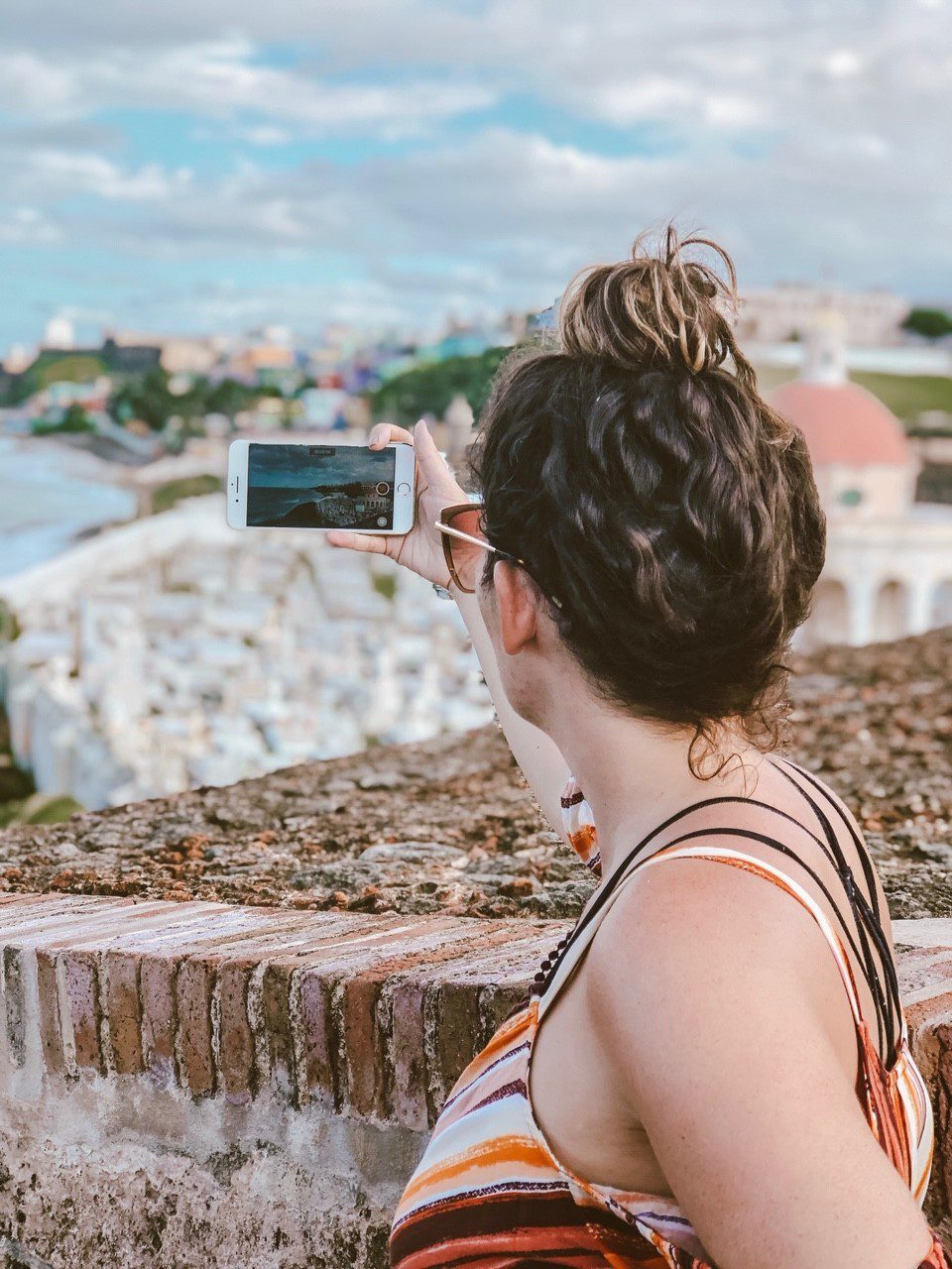 5 Amazing Reason to go on a Holland America cruise with Oprah Magazine by popular US lifestyle blog Fresh Mommy Blog: image of woman looking out over a city and taking a picture with her iphone.