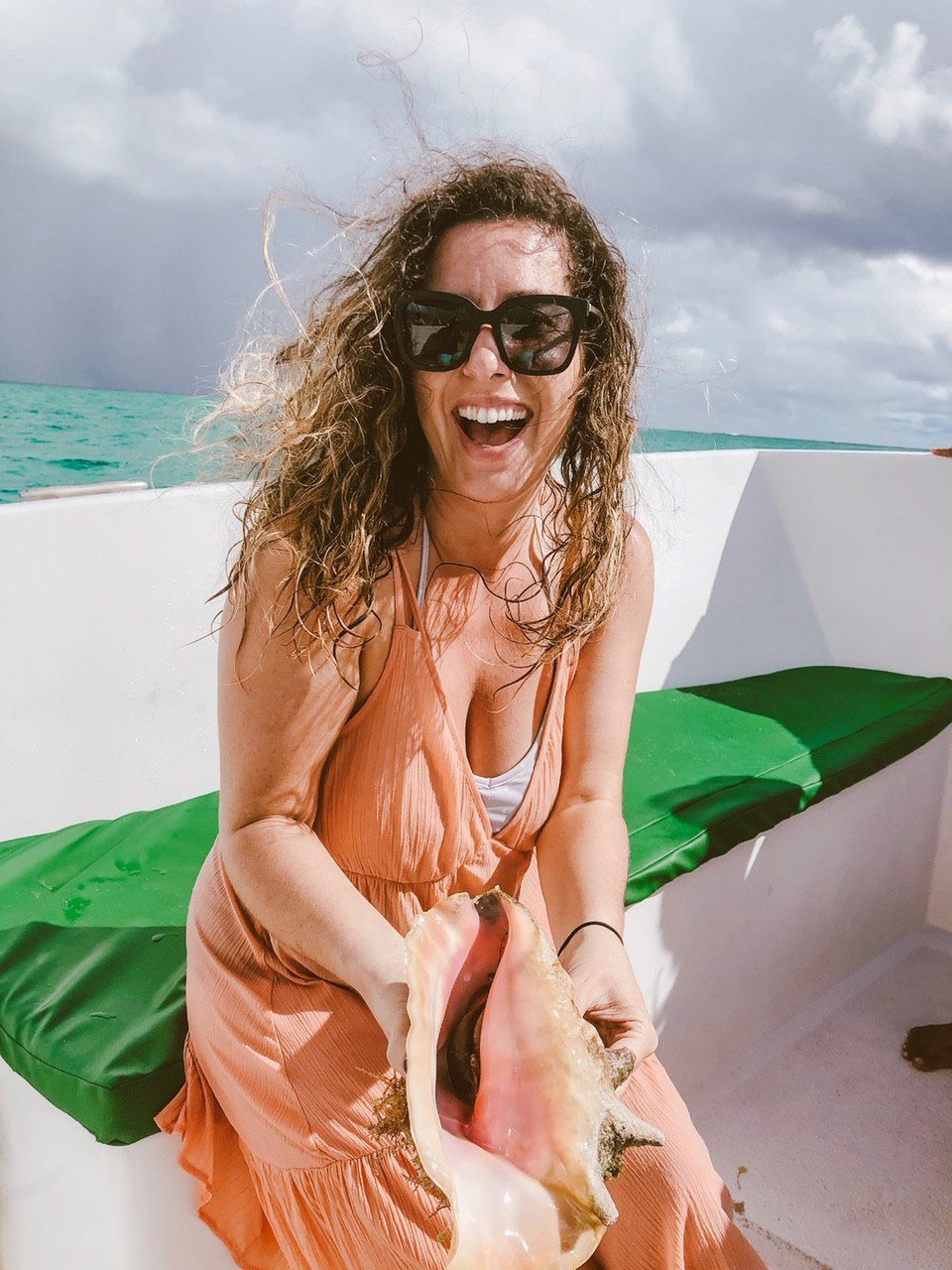 5 Amazing Reason to go on a Holland America cruise with Oprah Magazine by popular US lifestyle blog Fresh Mommy Blog: image of woman holding a large conk shell on a boat.