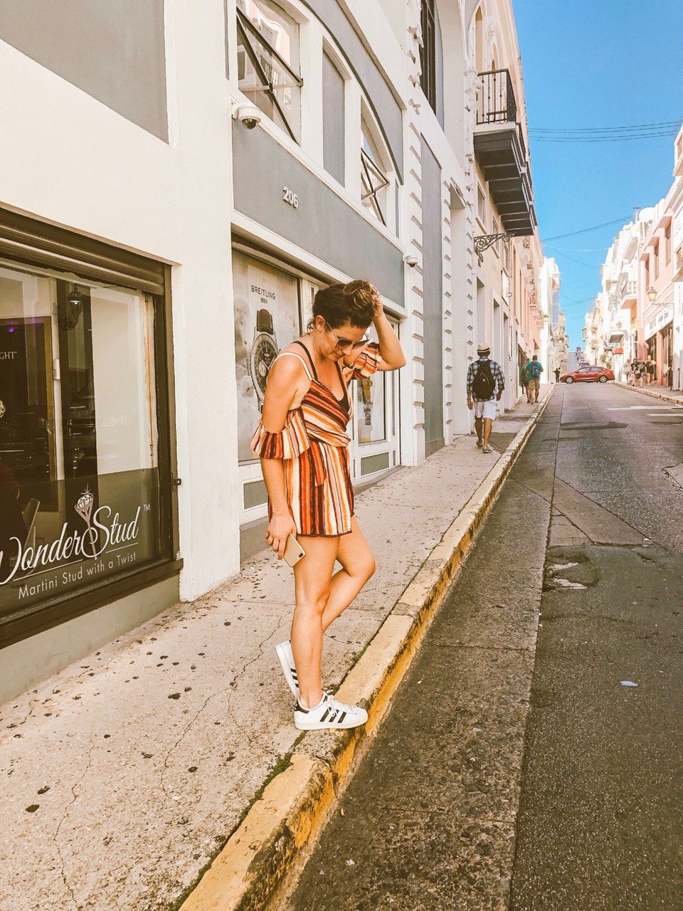 5 Amazing Reason to go on a Holland America cruise with Oprah Magazine by popular US lifestyle blog Fresh Mommy Blog: image of woman wearing a stripe cover up, large frame sunglasses, adidas sneakers, and standing on street curb in the Caribbean.