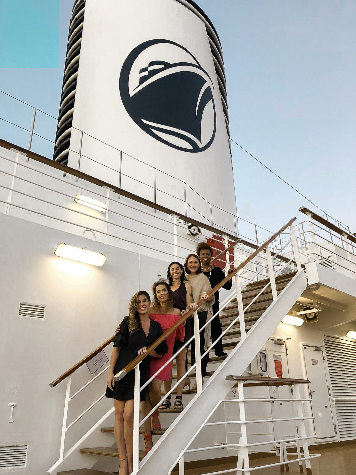 5 Amazing Reason to go on a Holland America cruise with Oprah Magazine by popular US lifestyle blog Fresh Mommy Blog: image of five women wearing cocktail dresses and standing on a exterior staircase on a Holland America cruise ship.