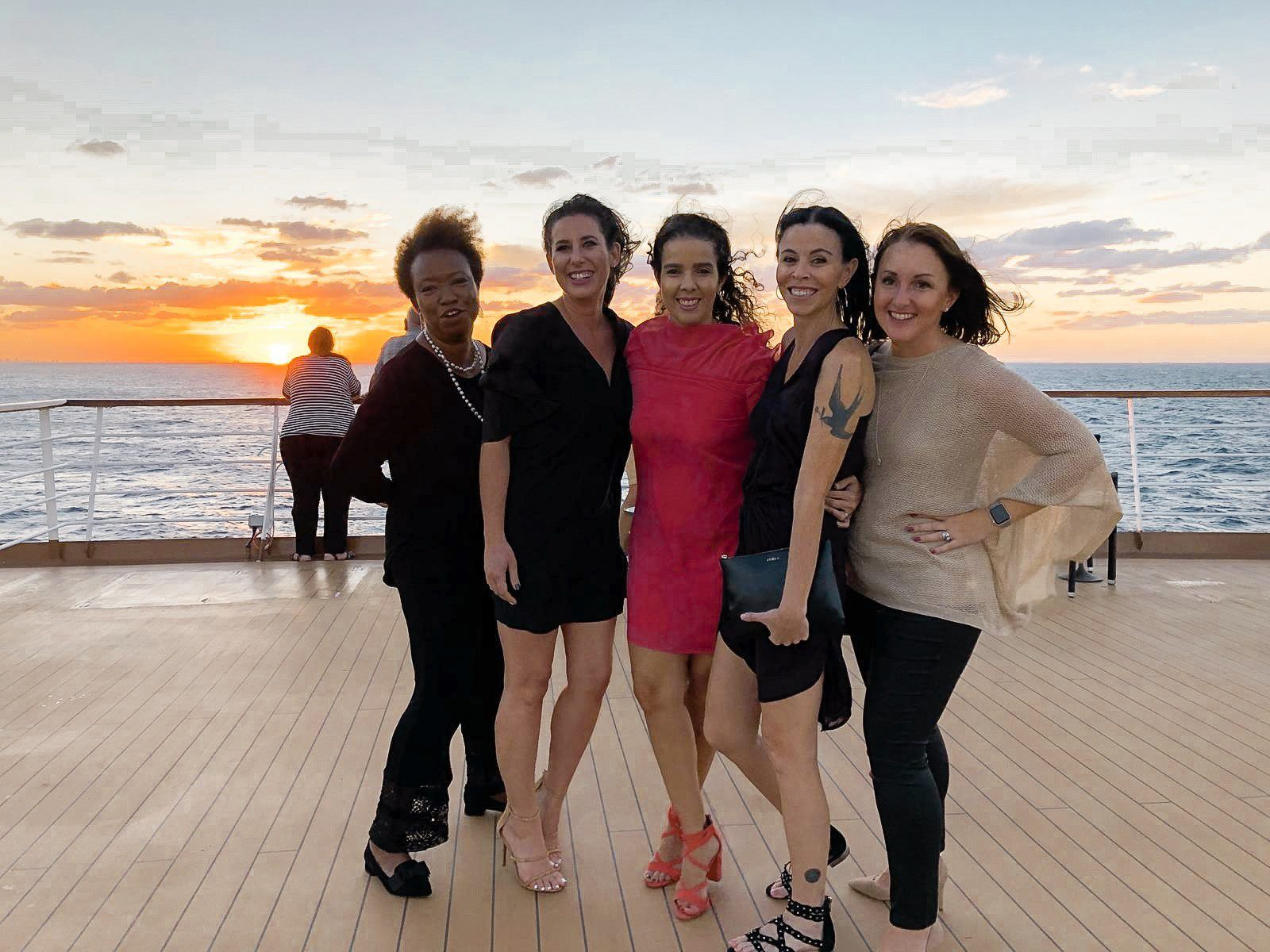 5 Amazing Reason to go on a Holland America cruise with Oprah Magazine by popular US lifestyle blog Fresh Mommy Blog: image of 5 women in cocktail dresses standing on the Holland America cruise ship deck at sunset