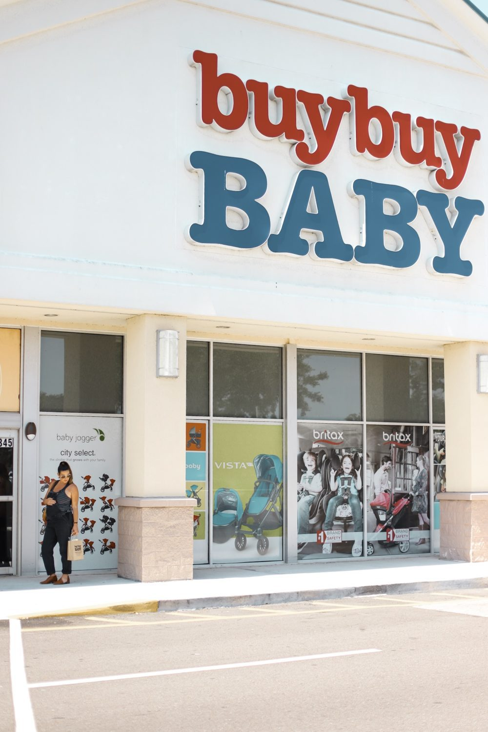 Useful Twin Products and Must Haves for Twins! Our Twin Registry Essentials - Splurge vs Steal by top US lifestyle blogger, Tabitha Blue of Fresh Mommy Blog | Baby Registry Must-Haves for Twins by popular US mom blog Fresh Mommy Blog: image of a pregnant woman standing outside of a buybuy Baby store.