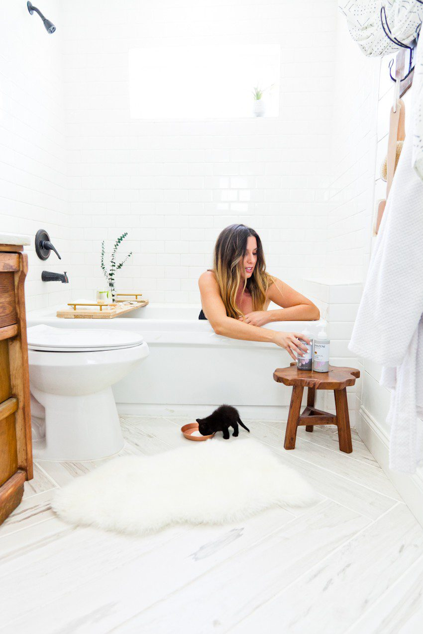 Kitten Care Tips: 5 Essentials you Need to Raise a Cat by popular lifestyel blogger Tabitha Blue of Fresh Mommy Blog: image of woman sitting in the tub with a black kitten on the bathroom floor next to the tub.