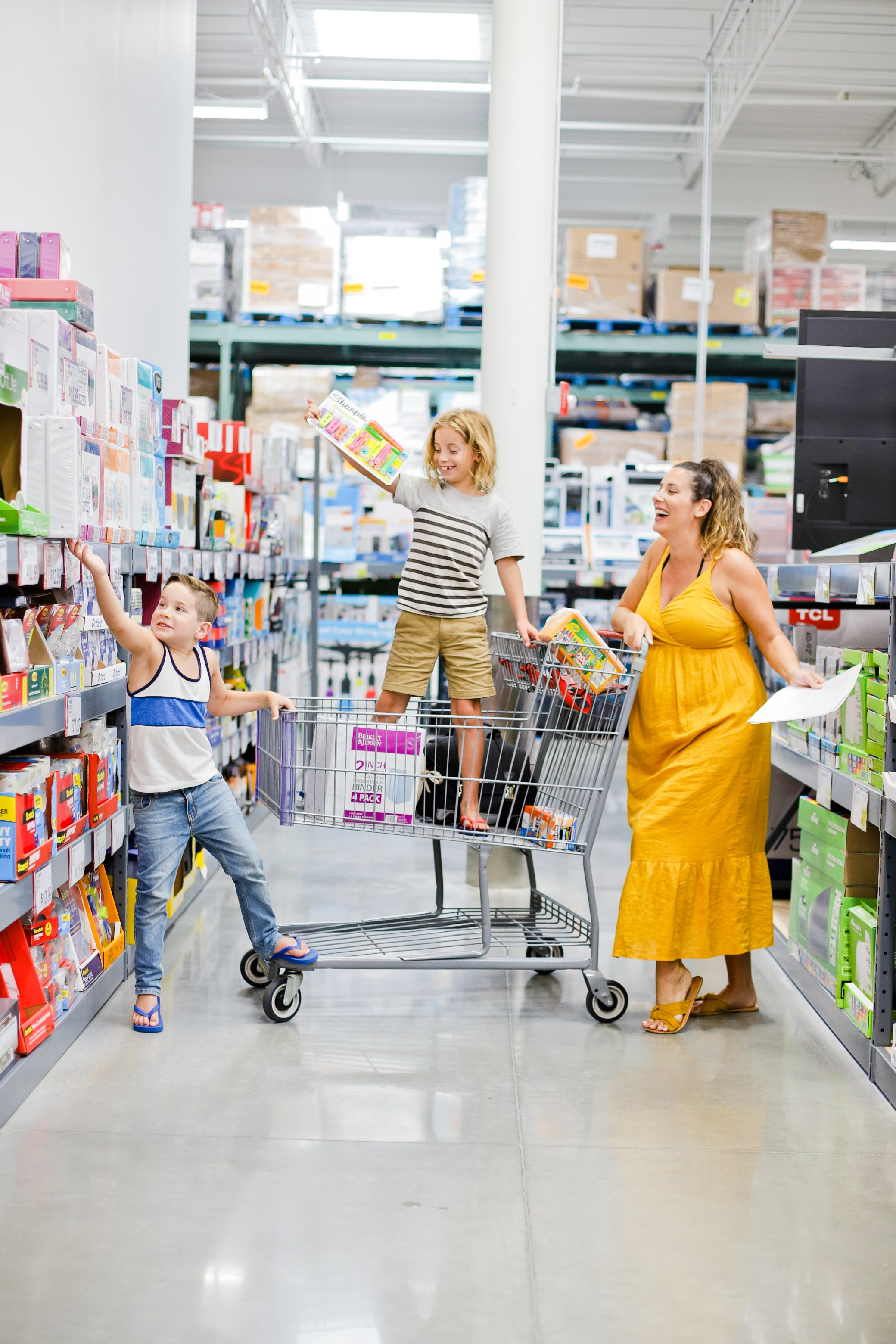 5 Sensational Strategies to Make Getting Ready for School Easy | How to Get Ready for School: 5 Sensational Strategies to Make Easy on your Family by popular Tampa life and style blog, Fresh Mommy: image of a woman standing in a school supply aisle at a store with her two young sons.