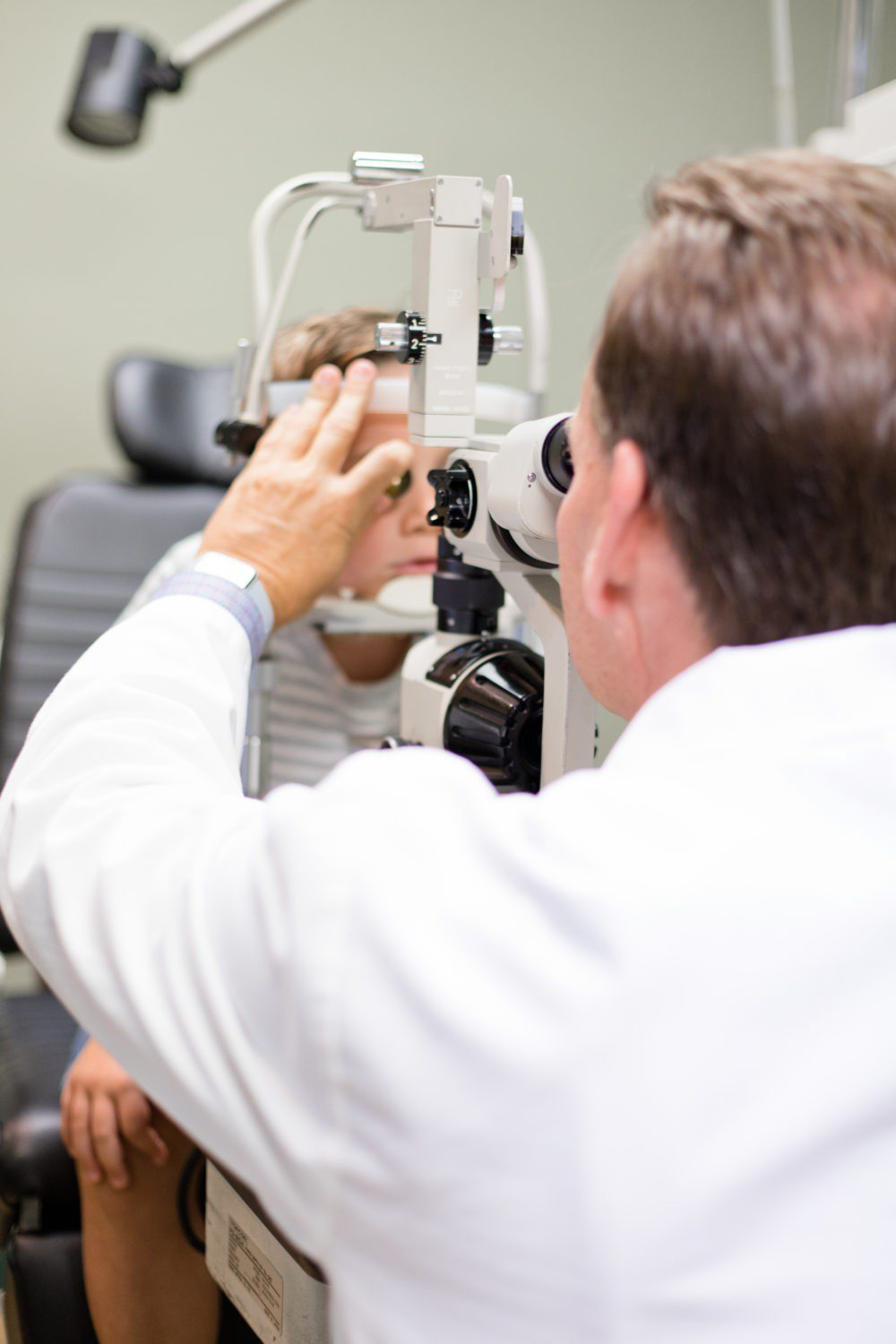 Back to School Eye Exam: How to Prepare your Child for a Successful Academic Year | Back to School Eye Exam: How to Prepare your Child for a Successful Academic Year by popular Florida lifestyle blog, Fresh Mommy Blog: image of a young boy getting his eyes examined by an eye doctor.