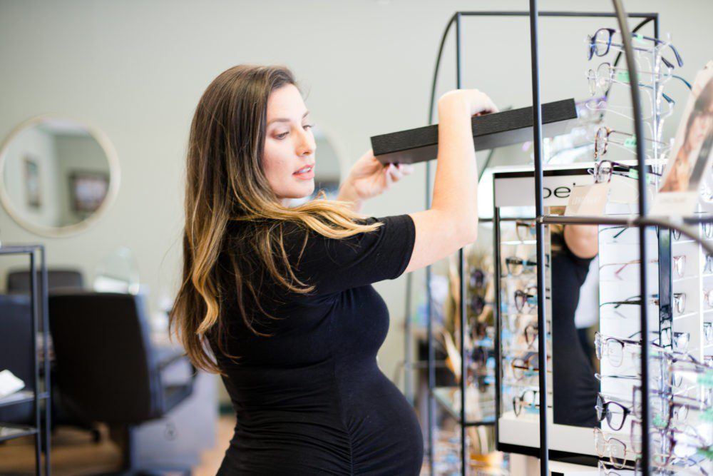 Back to School Eye Exam: How to Prepare your Child for a Successful Academic Year | Back to School Eye Exam: How to Prepare your Child for a Successful Academic Year by popular Florida lifestyle blog, Fresh Mommy Blog: image of a woman putting some glasses back on to a display rack.