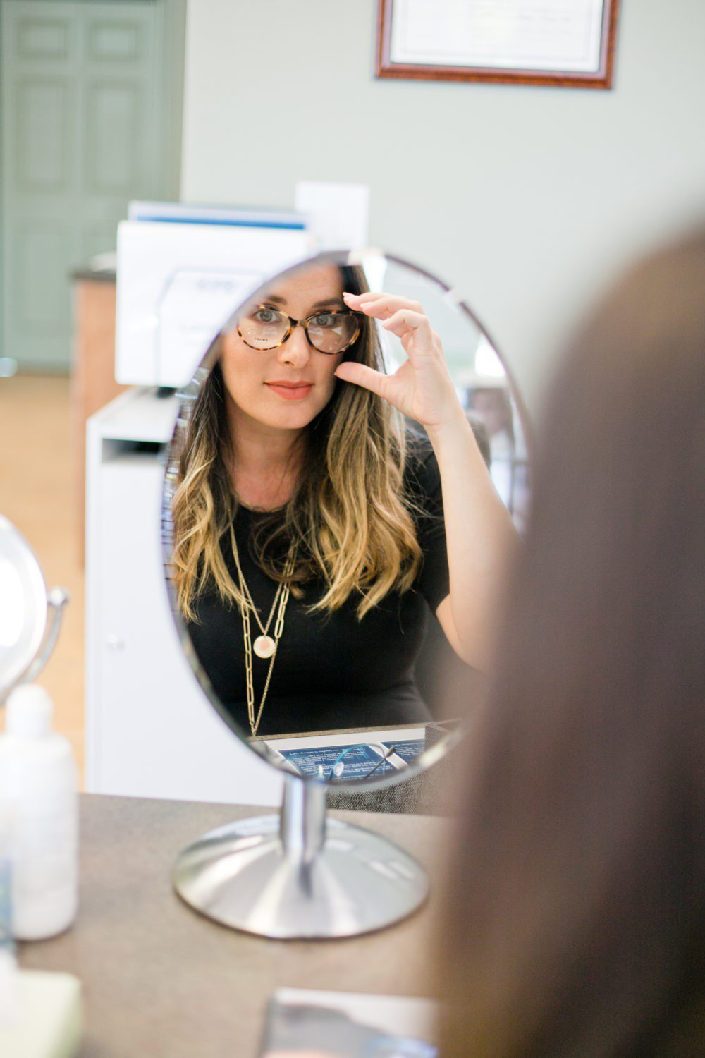 Back to School Eye Exam: How to Prepare your Child for a Successful Academic Year | Back to School Eye Exam: How to Prepare your Child for a Successful Academic Year by popular Florida lifestyle blog, Fresh Mommy Blog: image of a woman looking at herself in a mirror and trying on a pair of glasses.