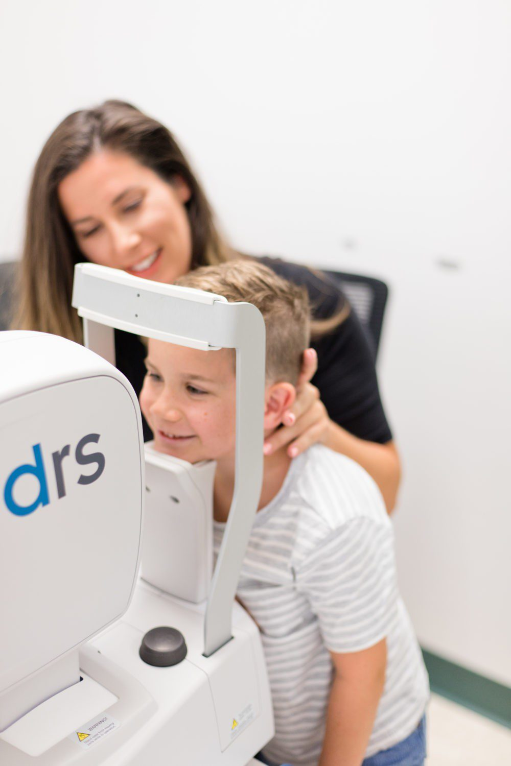 Back to School Eye Exam: How to Prepare your Child for a Successful Academic Year | Back to School Eye Exam: How to Prepare your Child for a Successful Academic Year by popular Florida lifestyle blog, Fresh Mommy Blog: image of a young boy getting his eyes examined.