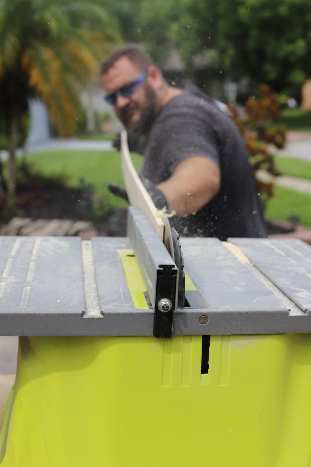 DIY for Covering Breaker Boxes: A Faux Cabinet Tutorial by popular Florida DIY blog, Fresh Mommy: image of a man cutting wood on a saw table.