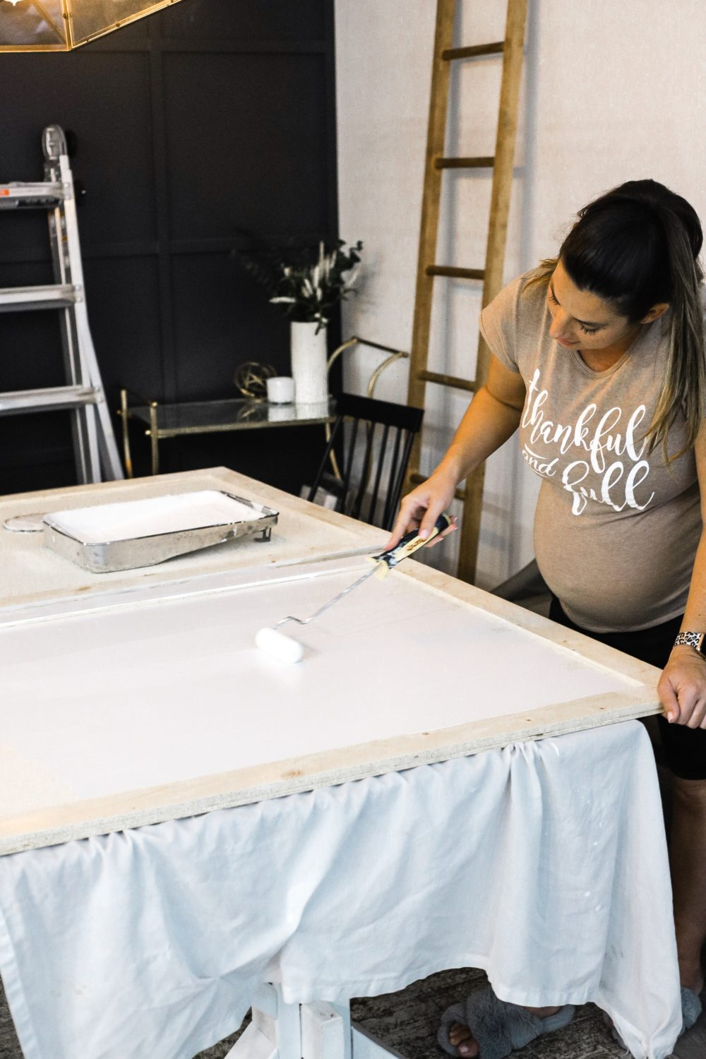 DIY for Covering Breaker Boxes: A Faux Cabinet Tutorial by popular Florida DIY blog, Fresh Mommy: image of a woman painting some cabinets.
