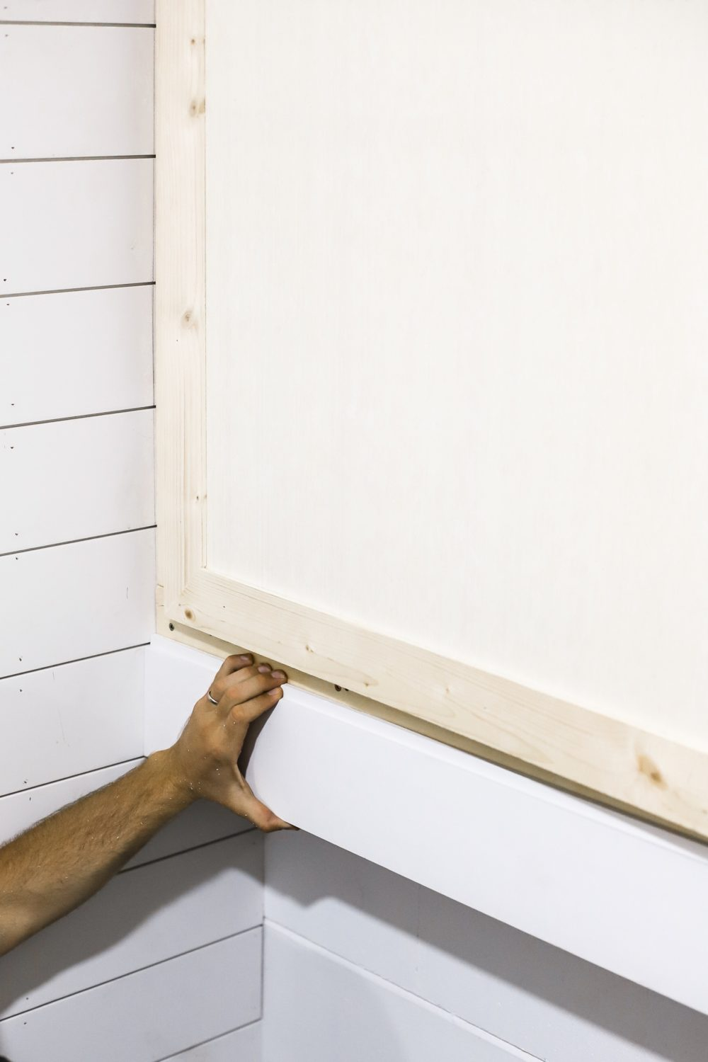 DIY for Covering Breaker Boxes: A Faux Cabinet Tutorial by popular Florida DIY blog, Fresh Mommy: image of a applying wood trim to his cabinets.