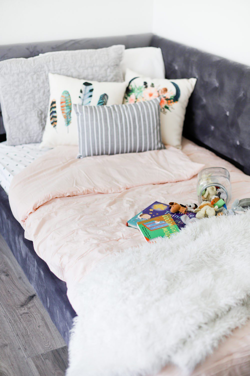 6 Best Tips to Transition Your Child from Crib to Toddler Bed: Aria's Big Girl Bed | 6 Best Tips to Transition Your Child from Crib to Toddler Bed: Aria's Big Girl Bed by popular Florida lifestyle blog, Fresh Mommy: image of a velvet tufted twin bed with toys and books on it.