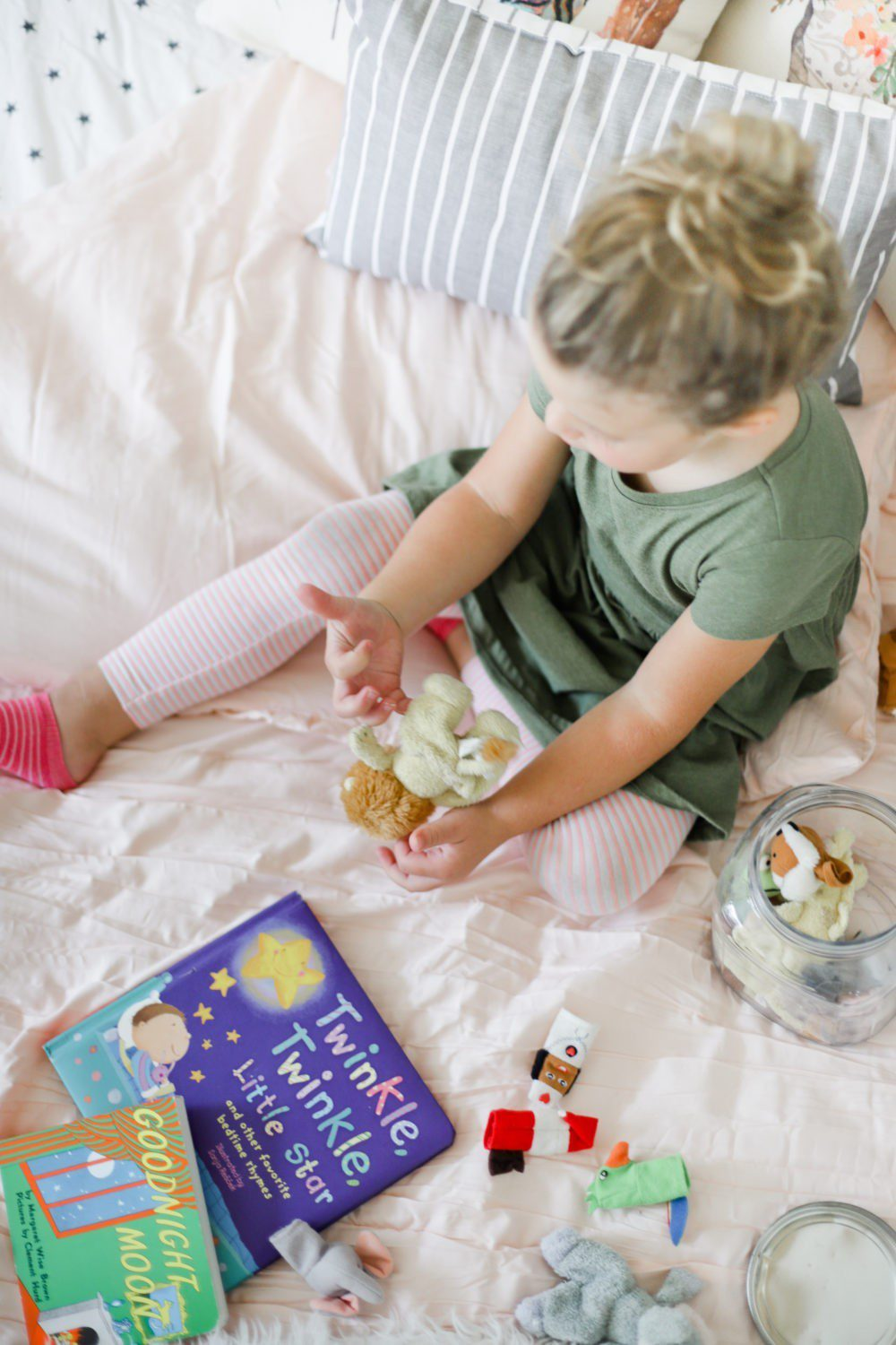 6 Best Tips to Transition Your Child from Crib to Toddler Bed: Aria's Big Girl Bed | 6 Best Tips to Transition Your Child from Crib to Toddler Bed: Aria's Big Girl Bed by popular Florida lifestyle blog, Fresh Mommy: image of a little girl playing with finger puppets on her bed.