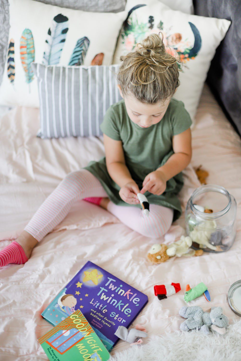 6 Best Tips to Transition Your Child from Crib to Toddler Bed: Aria's Big Girl Bed in our Shared Girl's Room | 6 Best Tips to Transition Your Child from Crib to Toddler Bed: Aria's Big Girl Bed by popular Florida lifestyle blog, Fresh Mommy: image of a little girl playing with finger puppets on her bed.