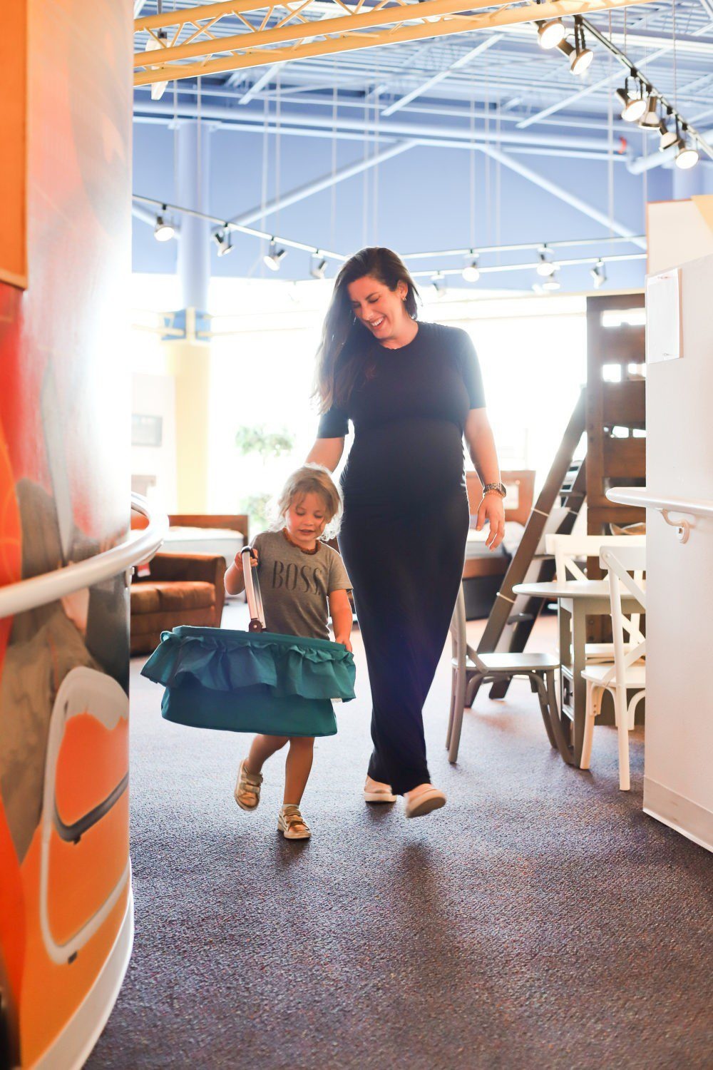 6 Best Tips to Transition Your Child from Crib to Toddler Bed: Aria's Big Girl Bed | 6 Best Tips to Transition Your Child from Crib to Toddler Bed: Aria's Big Girl Bed by popular Florida lifestyle blog, Fresh Mommy: image of a mom walking through a furniture store with her daughter.