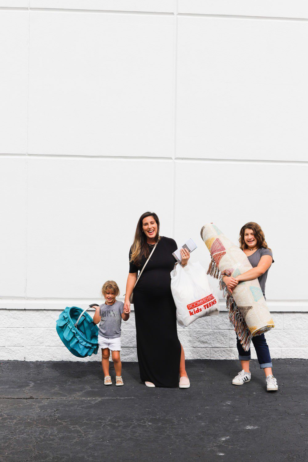 6 Best Tips to Transition Your Child from Crib to Toddler Bed: Aria's Big Girl Bed | 6 Best Tips to Transition Your Child from Crib to Toddler Bed: Aria's Big Girl Bed by popular Florida lifestyle blog, Fresh Mommy: image of a mom and her two daughters standing outside of a furniture store with a bassinet and an area rug.