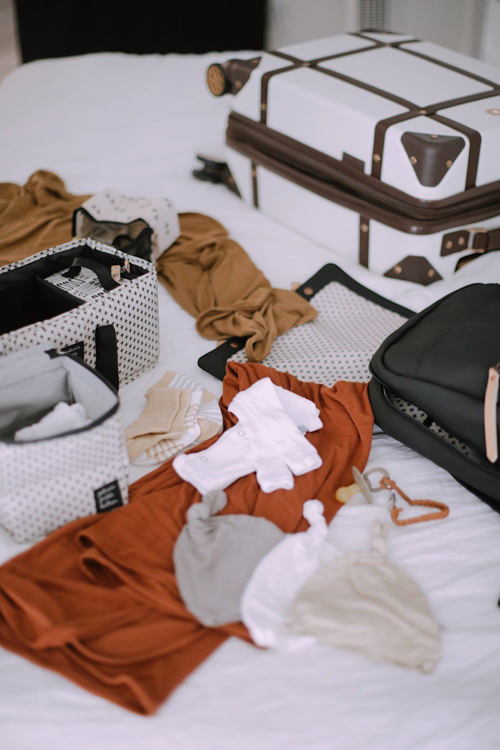 No-Fuss Hospital Bag Must-Haves You Need for Delivery and Recovery including diaper bag necessities for baby. What to pack in a delivery bag for mama. A go bag for dad. What to pack for a c section and what you DON'T need to pack in a hospital bag. | Hospital Bag Essentials for Twins by popular Florida life and style blog, Fresh Mommy: image of a Petunia Pickle Bottom Meta Diaper Backpack, baby onesies, socks, baby beanies, and a pacifier clip.