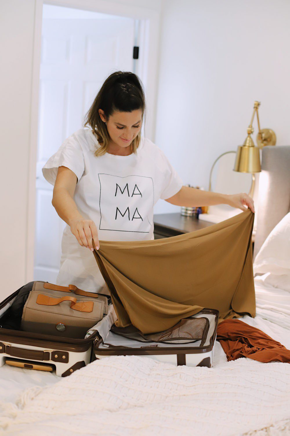 No-Fuss Hospital Bag Must-Haves You Need for Delivery and Recovery! What to pack in a delivery bag for mama. A go bag for dad. What to pack for a c section and what you DON'T need to pack in a hospital bag. | Hospital Bag Essentials for Twins by popular Florida life and style blog, Fresh Mommy: image of a pregnant woman packing her hospital bag.