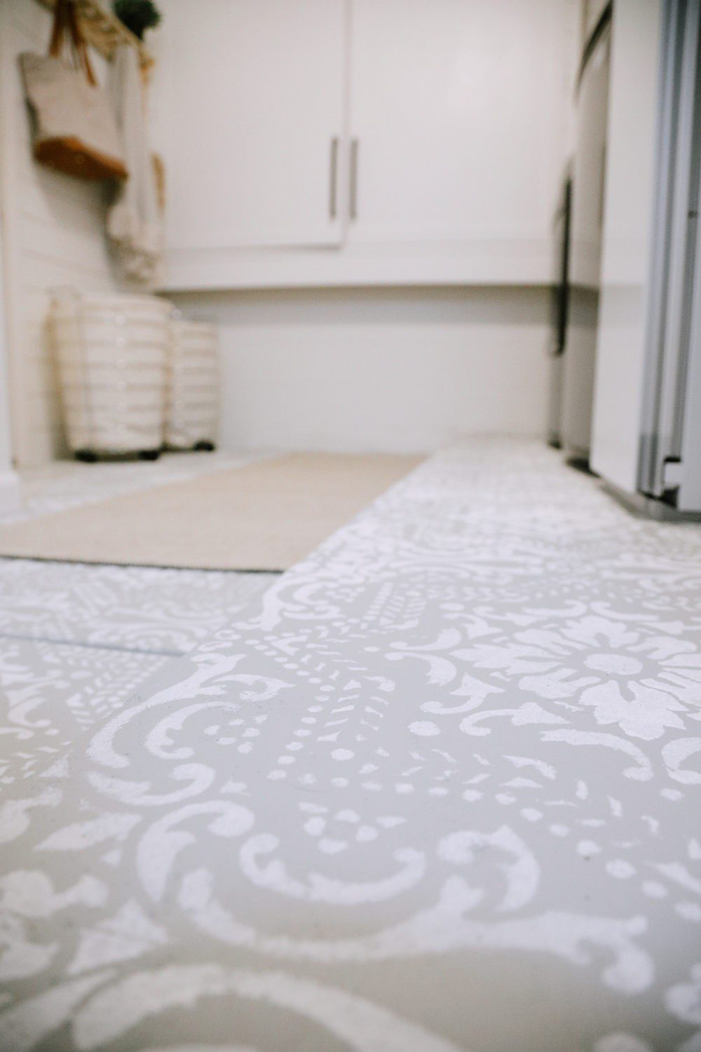How We Designed a Family Friendly Laundry Room in our Garage - The Reveal! Stenciled floors, DIY covers for breaker boxes and utilities, large capacity appliances, organization tips and more! | Laundry Room DIY: How to Paint a Cement Floor with Stencils by popular home decor blog, Fresh Mommy: image of painted cement floor.