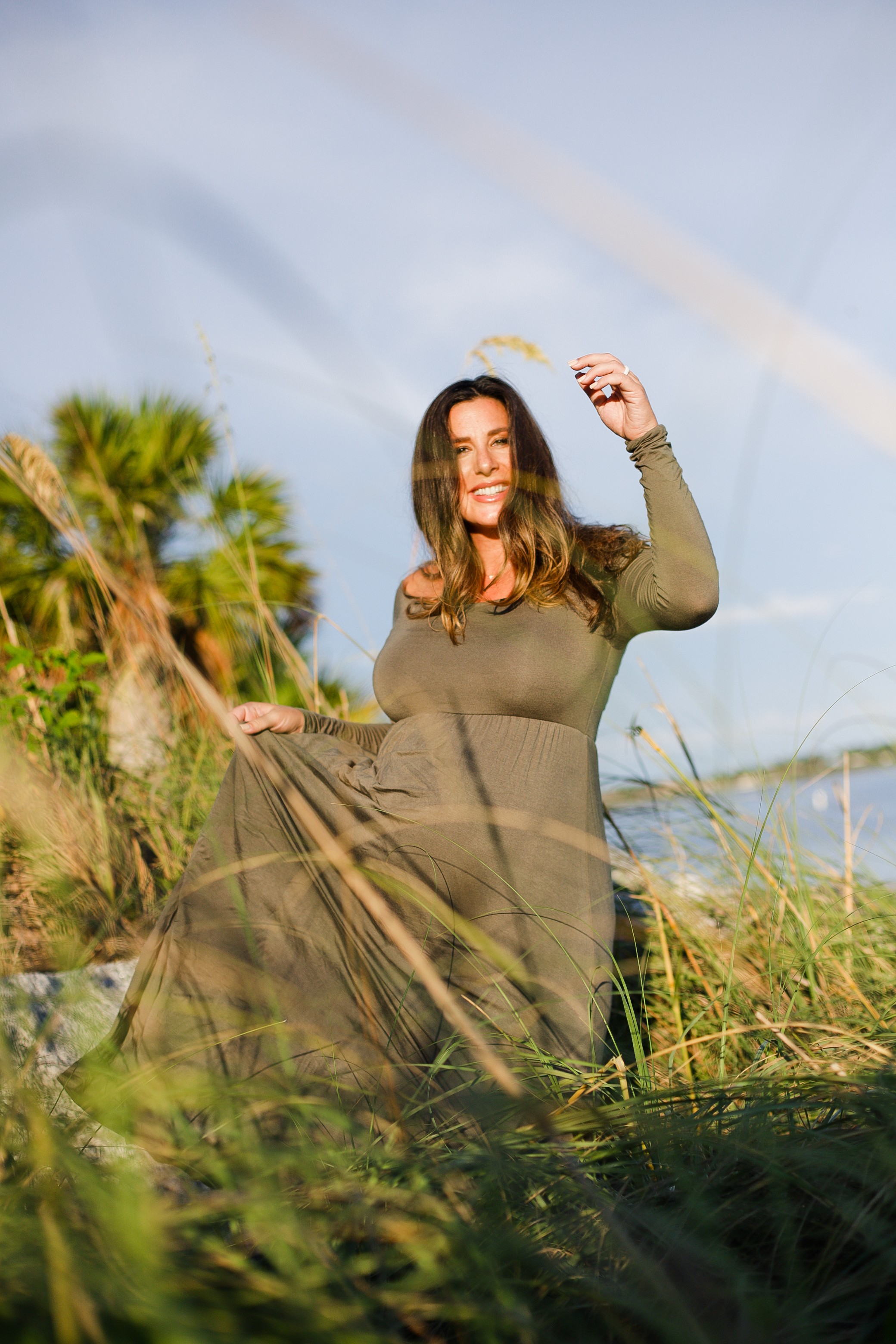 Maternity in olive green dress from Pink Blush Maternity, plus other olive green dress options! Beach maternity pictures and pregnancy photoshoot ideas from top Florida lifestyle blogger Tabitha Blue of Fresh Mommy Blog. | A Beach Maternity Photoshoot in Olive Green by popular Florida life and style blog, Fresh Mommy: image of a woman standing outside at the beach and wearing a Pink Blush Olive Solid Off Shoulder Maternity Maxi Dress.