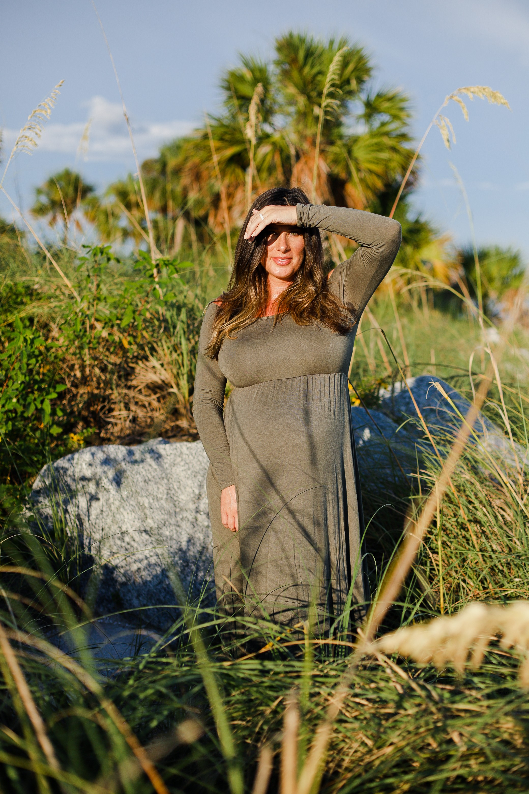 Twin Maternity Photos at the Beach | A Beach Maternity Photoshoot in Olive Green by popular Florida life and style blog, Fresh Mommy: image of a woman standing outside at the beach and wearing a Pink Blush Olive Solid Off Shoulder Maternity Maxi Dress.
