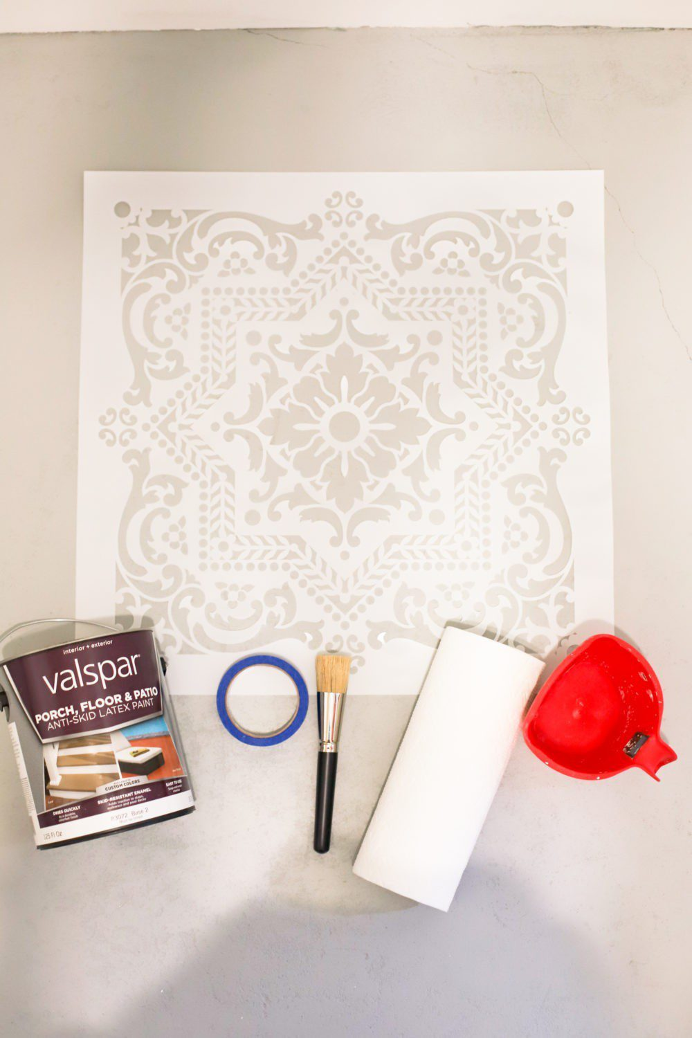 Laundry Room DIY: How to Paint a Cement Floor with Stencils | Laundry Room DIY: How to Paint a Cement Floor with Stencils by popular home decor blog, Fresh Mommy: image of a stencil, Valspar porch and floor paint, painters tape, paint brush, paint bowl, and paint roller.